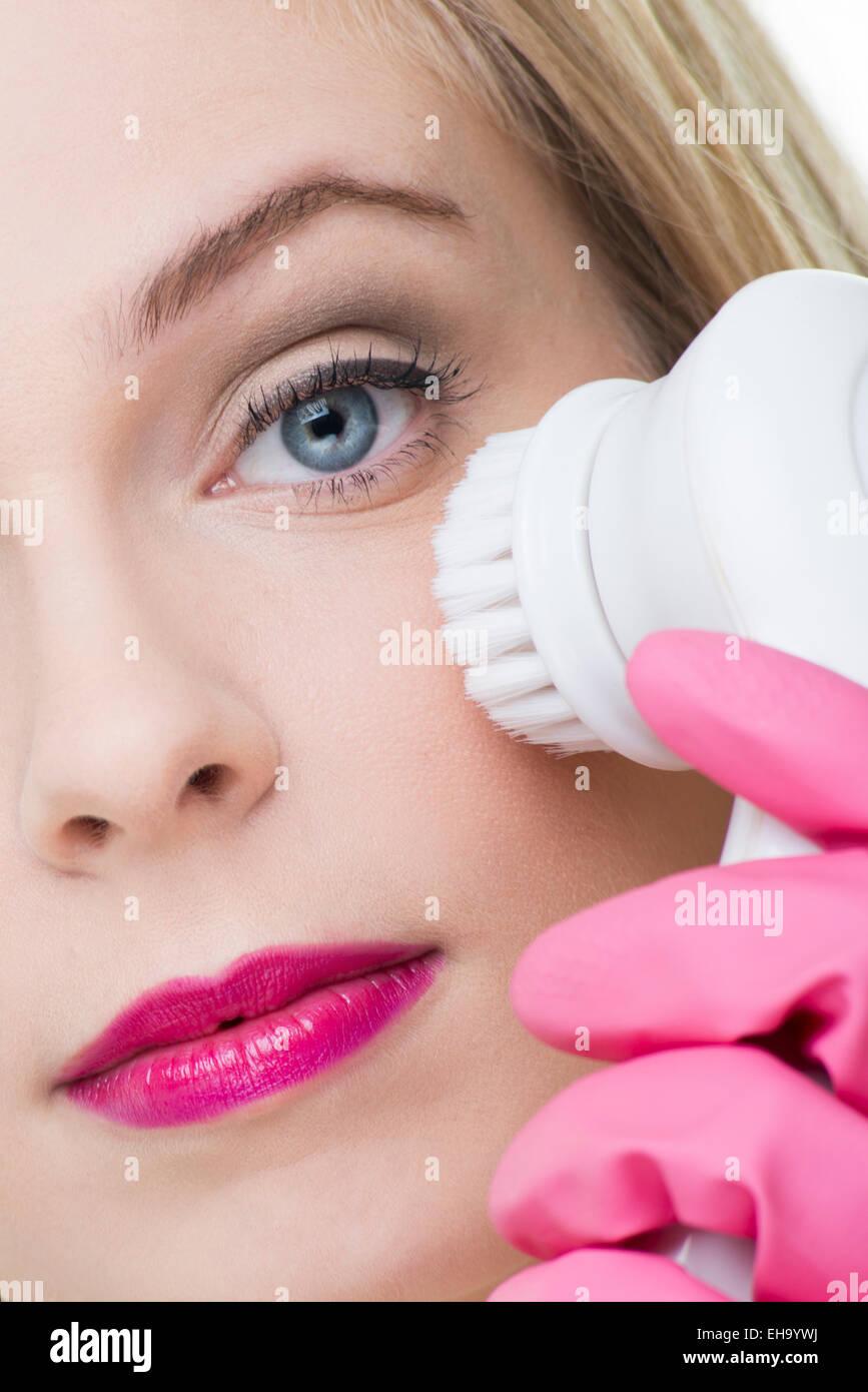 Nettoyage ethnique femme son visage à l'aide d'une brosse de nettoyage en profondeur Photo Stock