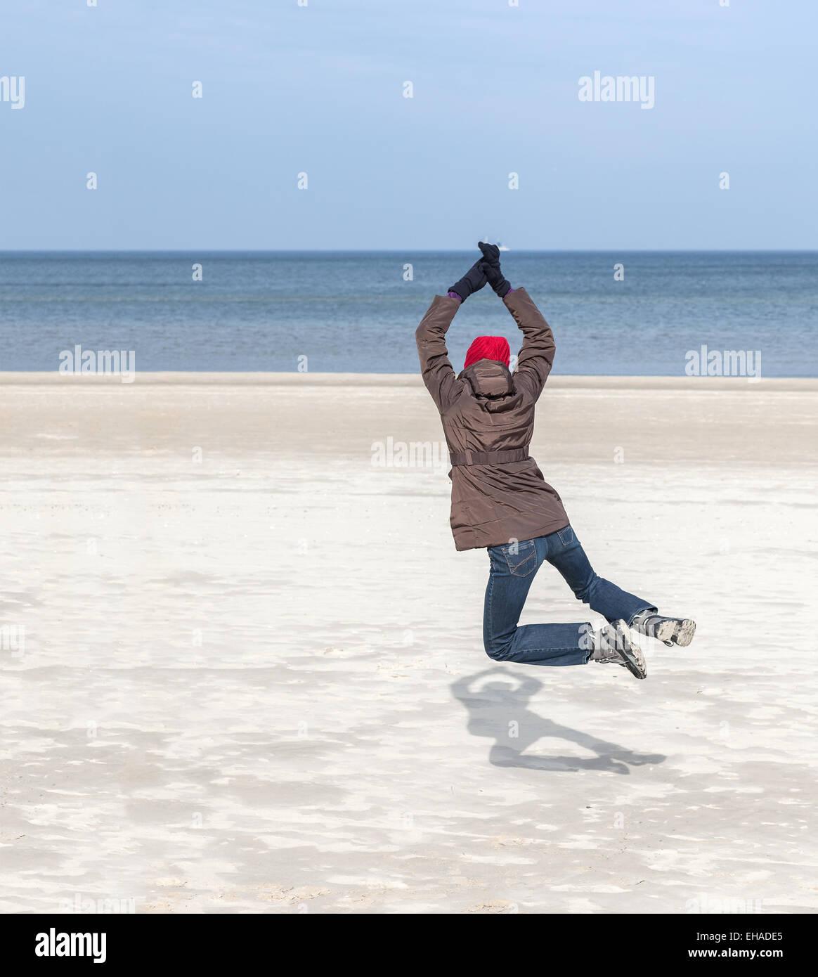 Femme sautant sur la plage, l'hiver de vie actif concept, l'espace pour le texte. Photo Stock