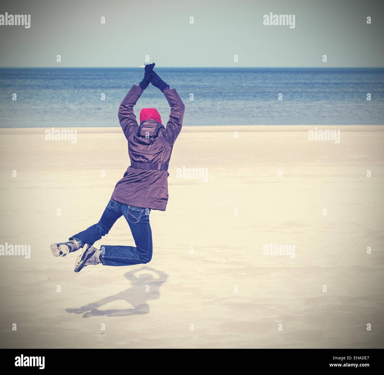 Retro photo filtrée de femme sautant sur la plage, l'hiver de vie actif concept, l'espace pour le texte. Photo Stock