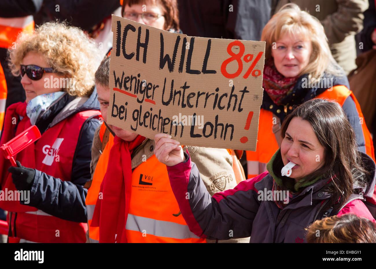 """Schwerin, Allemagne. Mar 11, 2015. Un manifestant porte un signe qui se lit 'JE wan 8 p. 100 de moins d'heures d'enseignement sur le même salaire' comme elle prend part avec des milliers de membres du personnel des agents de la fonction publique dans le cadre d'un rassemblement du Syndicat des enseignants de l'allemand 'GEW', 'unifiée des services Ver.di' et le Syndicat de la police """"PIB"""" à Schwerin, Allemagne, 11 mars 2015. Les syndicats exigent un 5.5 pour cent et au moins 175 euros par mois d'augmentation de salaire pour les travailleurs du secteur public. Photo: Jens Buettner/dpa/Alamy Live News Banque D'Images"""