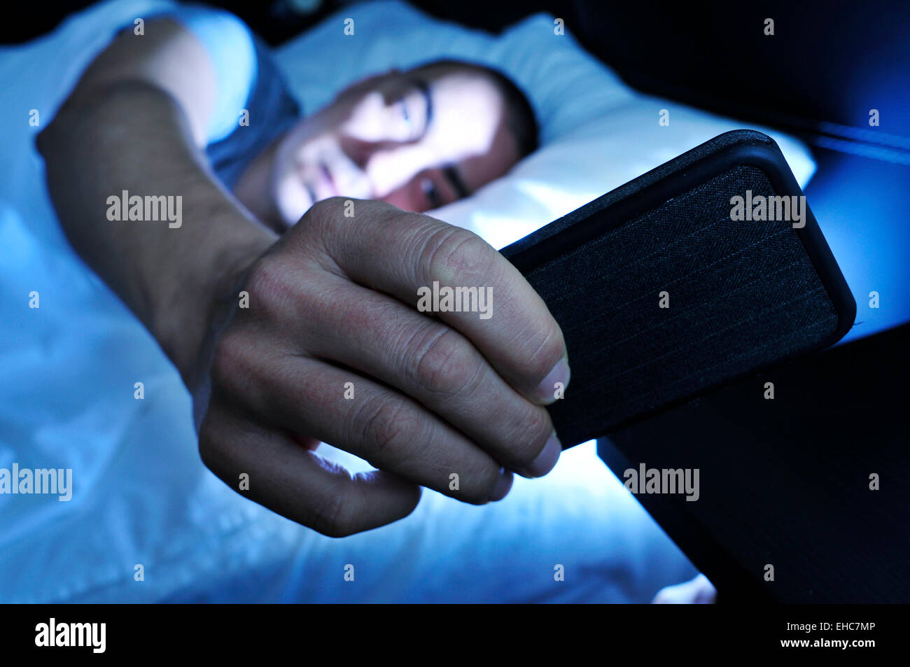 Libre d'un jeune homme dans le lit regardant le smartphone à nuit Photo Stock