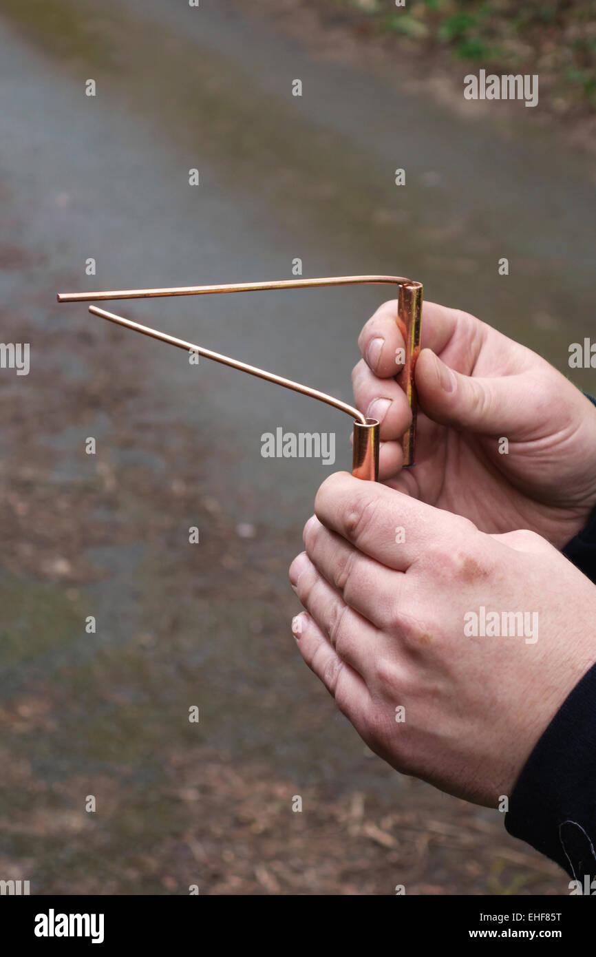 Un ingénieur de l'eau utilise du cuivre rods devinants pour tracer le cours d'une conduite souterraine Photo Stock