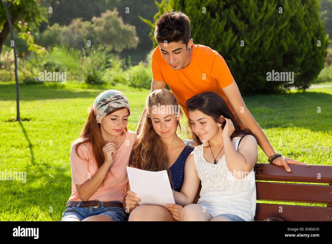 Lecture au parc. Groupe de filles est assise sur un banc et la lecture alors qu'un garçon est à la recherche à l'épaule Banque D'Images