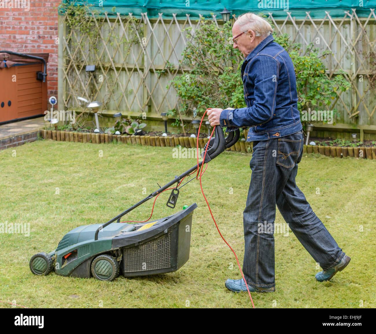 Vieil homme de tondre la pelouse dans un jardin. Photo Stock