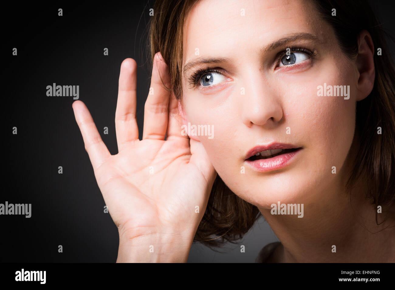 Femme tenant la main à son oreille. Photo Stock