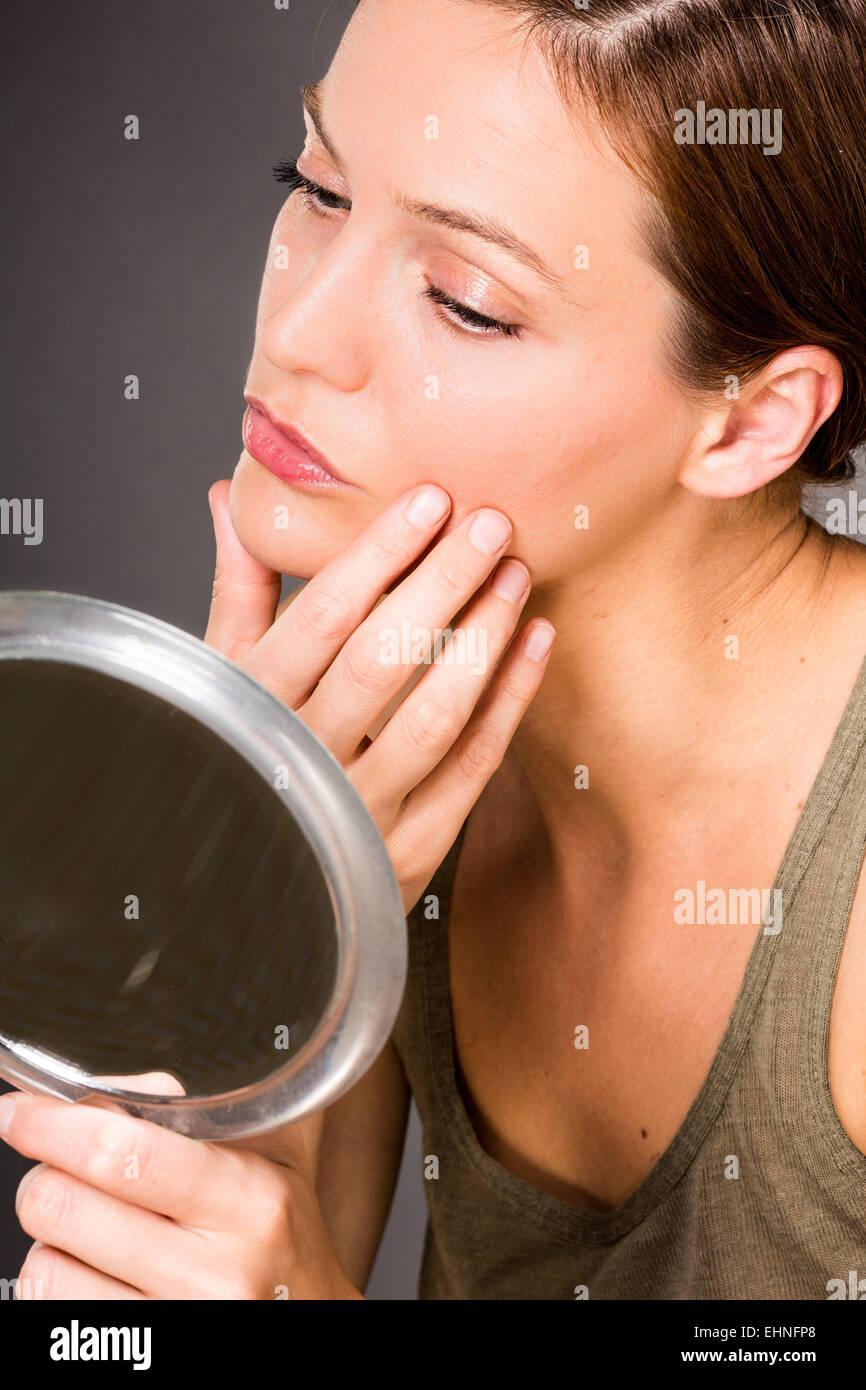 Femme contrôler son visage dans le miroir. Photo Stock