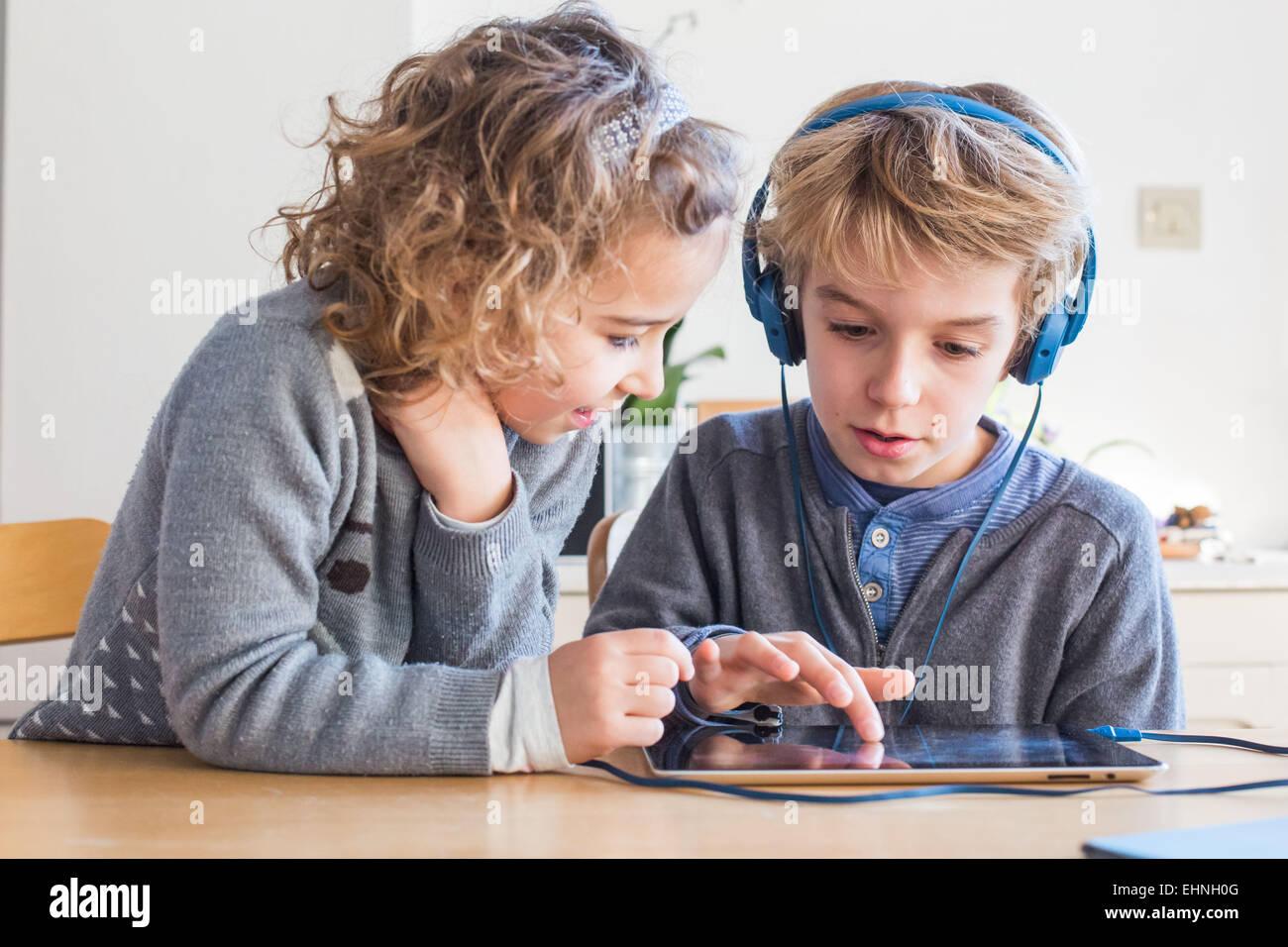5 ans, fille et garçon de 8 ans, à l'aide de l'ordinateur tablette. Photo Stock