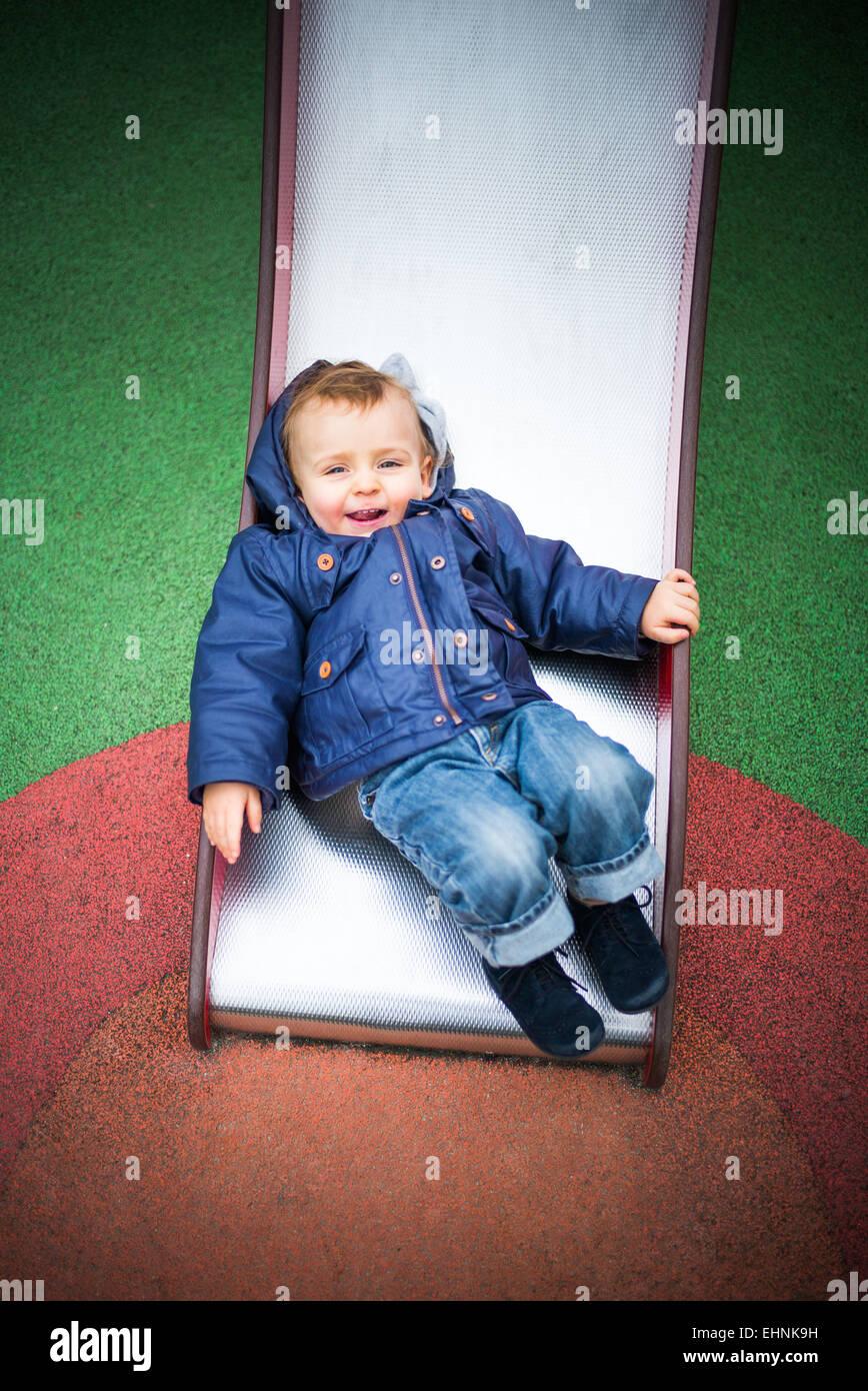 18 mois bébé garçon sur une diapositive dans une aire de jeux. Photo Stock