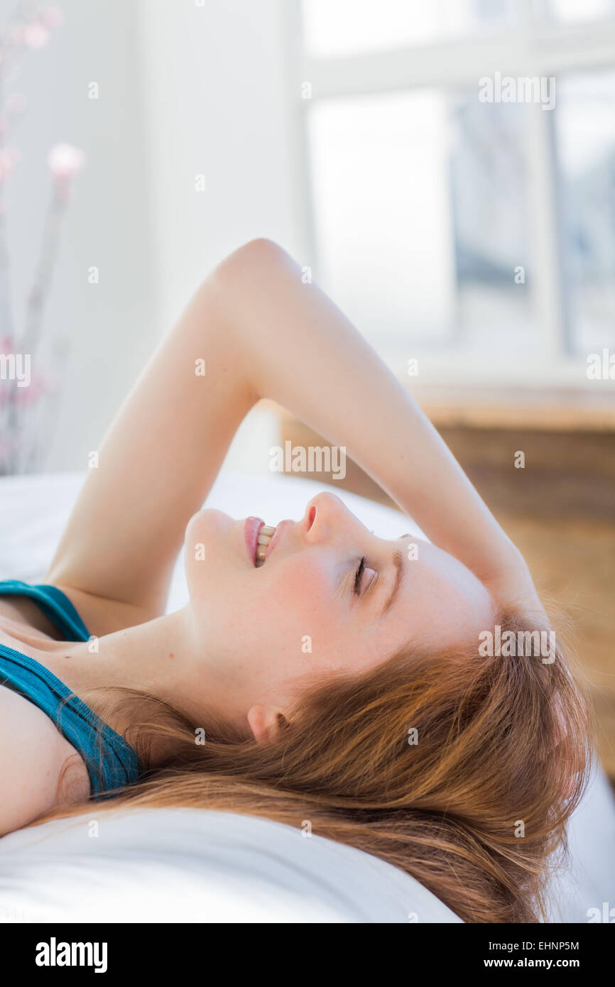 Femme portant sur bed smiling Photo Stock