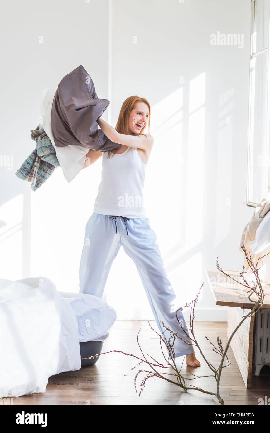 Femme faisant le lit. Banque D'Images
