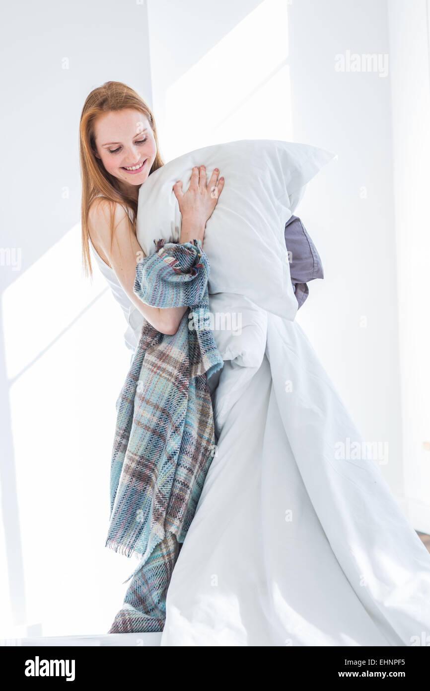 Femme faisant le lit. Photo Stock