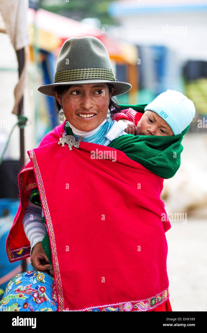 L'Équateur, jeune femme autochtone avec bébé portant cape rouge et un chapeau Photo Stock