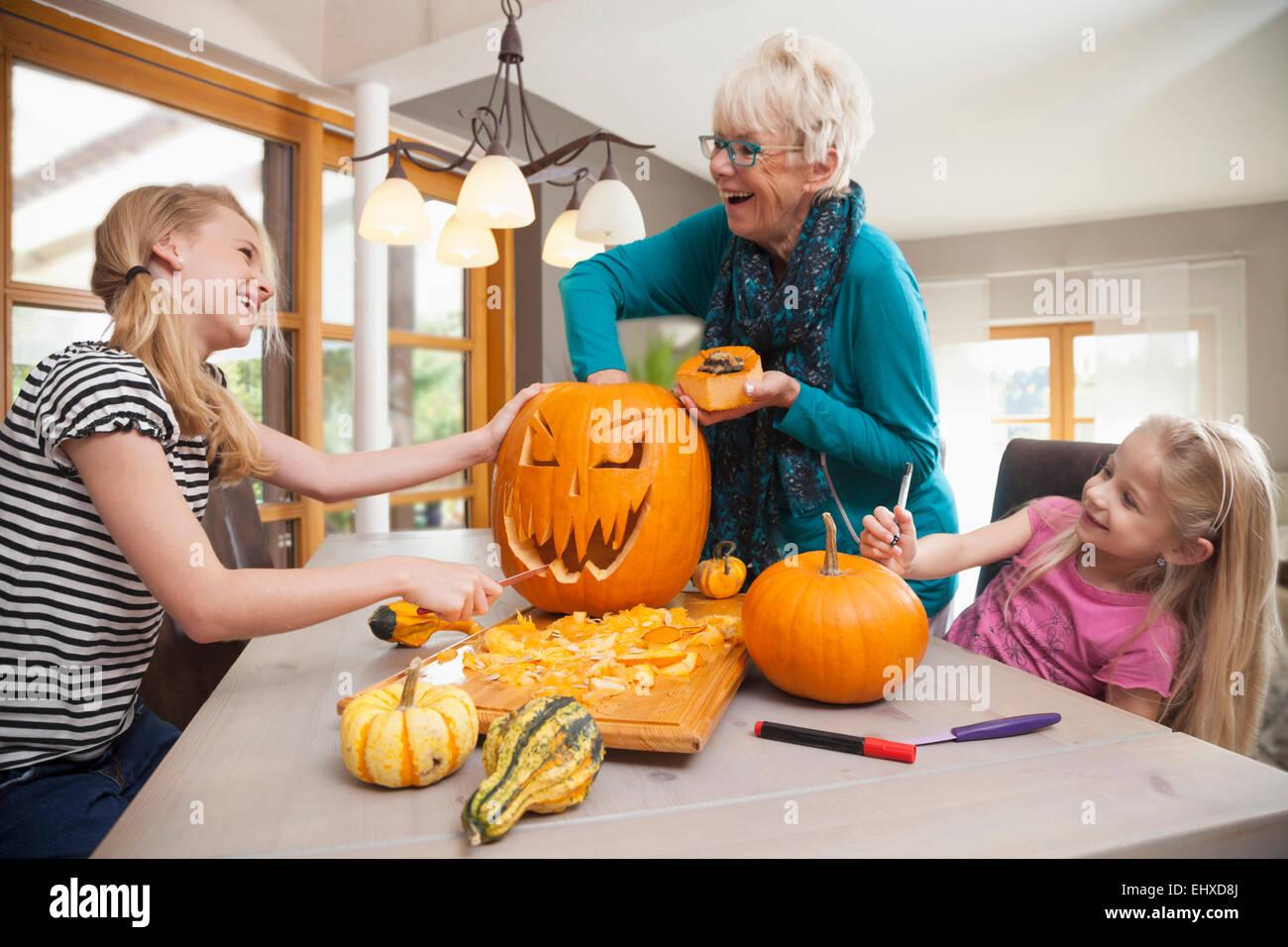 Senior woman sculpture de citrouille Halloween avec ses petites-filles, Bavière, Allemagne Photo Stock