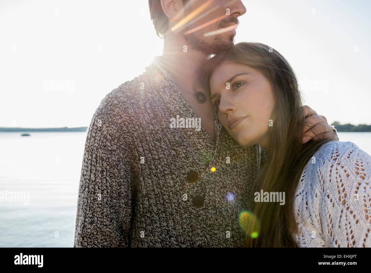 Jeune couple hugging sunset lake Banque D'Images