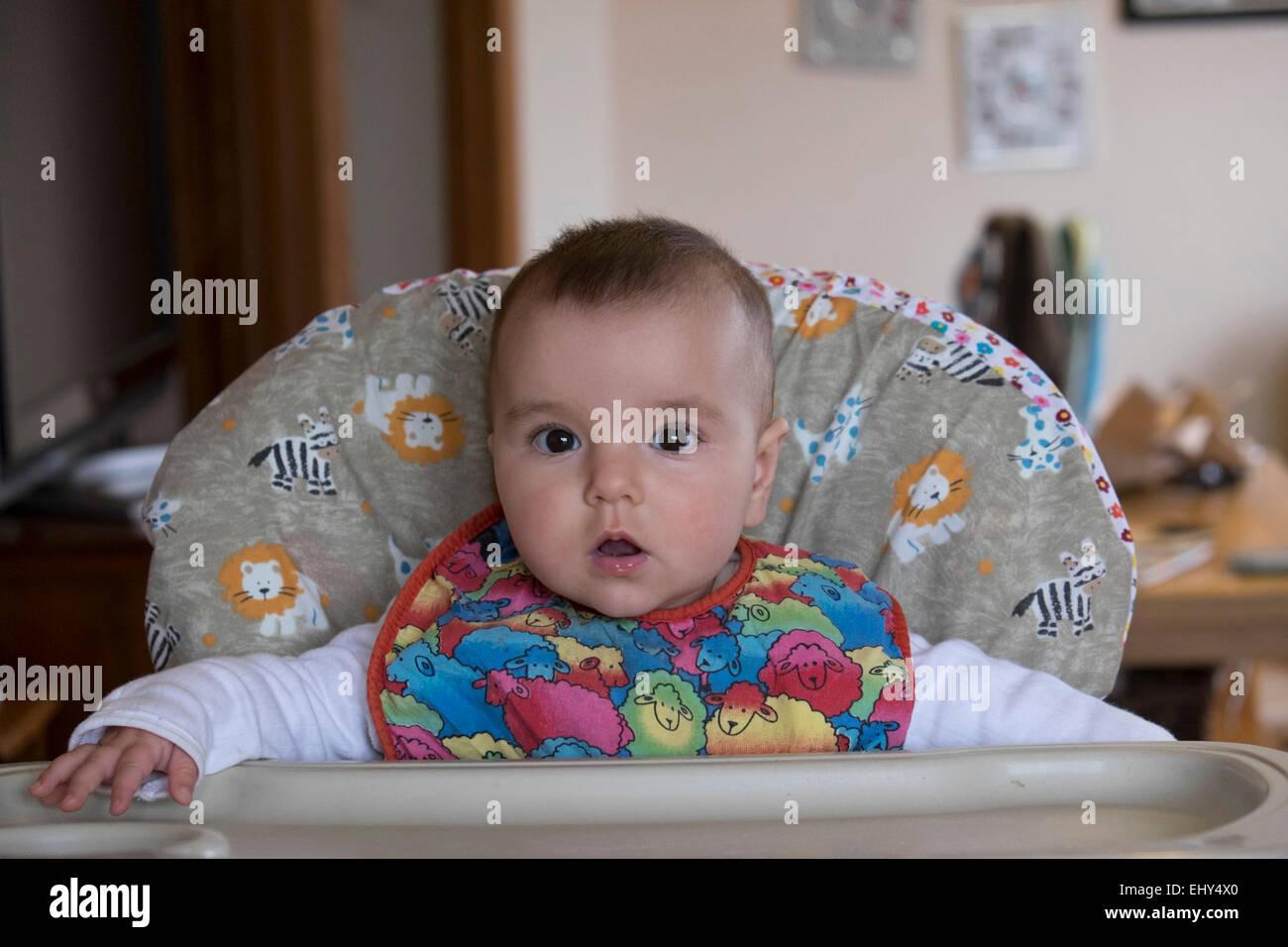 8 mois bébé fille assise dans une chaise haute photo stock
