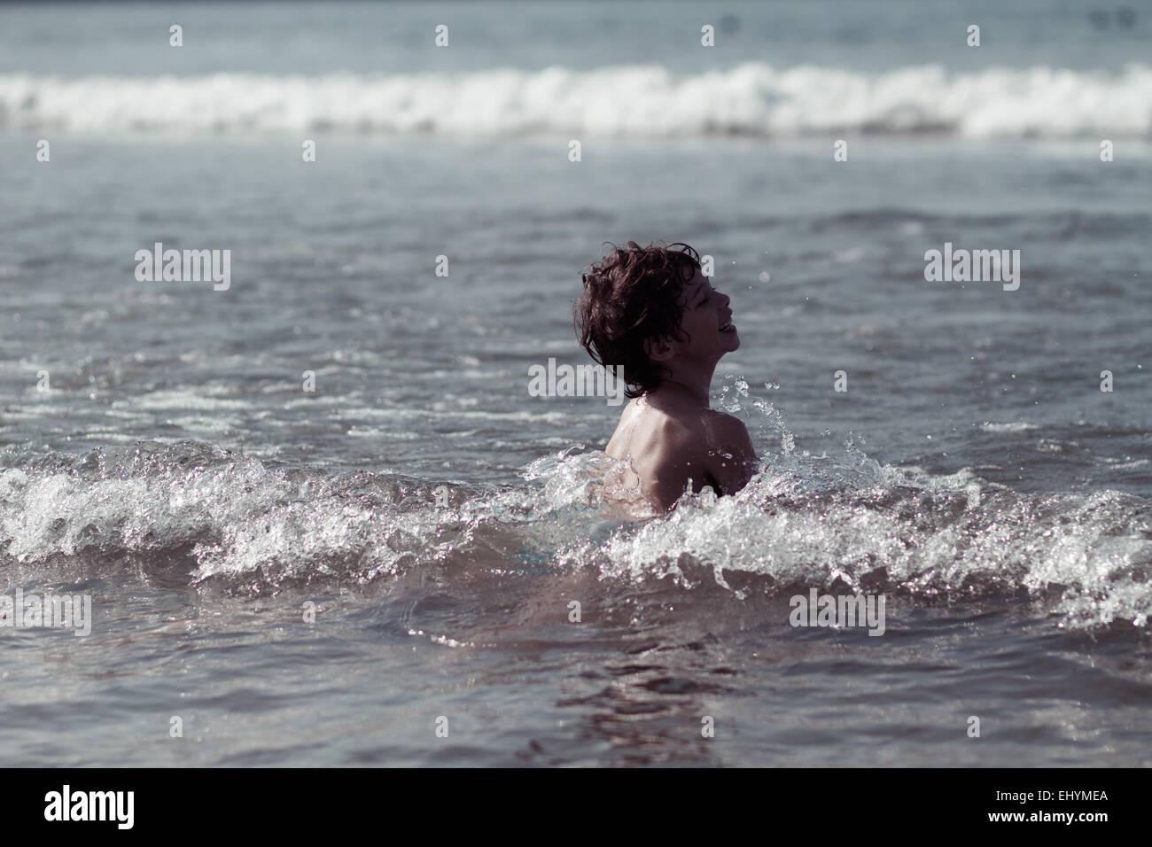 Garçon jouant dans les vagues, Brésil Photo Stock