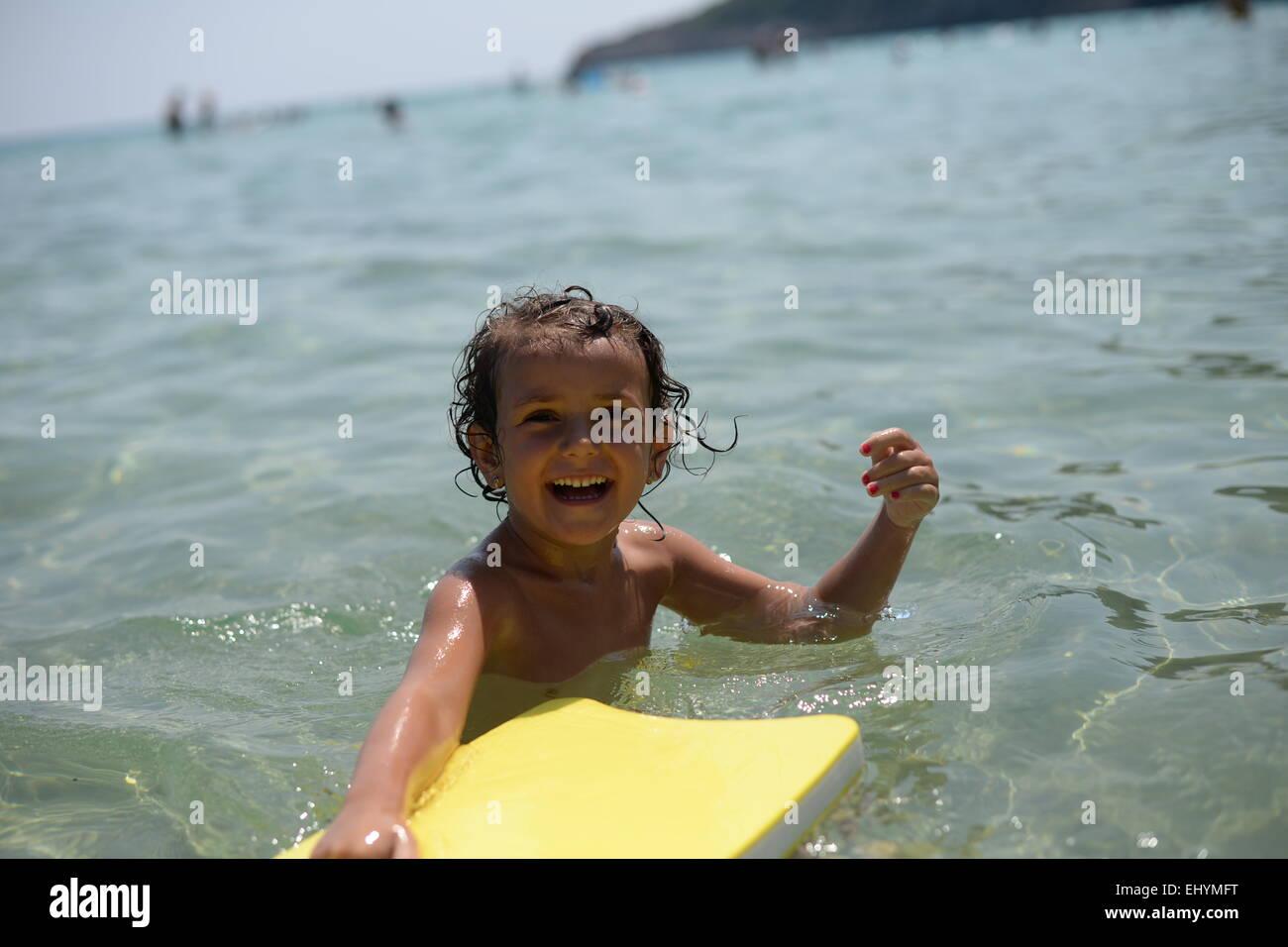 Smiling girl jouant avec un flotteur dans la mer, Thassos, Grèce Photo Stock