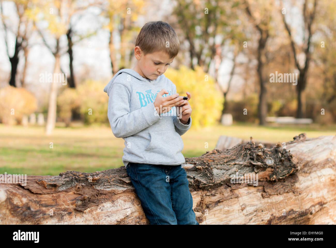 Boy leaning against tree trunk jouant sur appareil mobile dans le parc Photo Stock