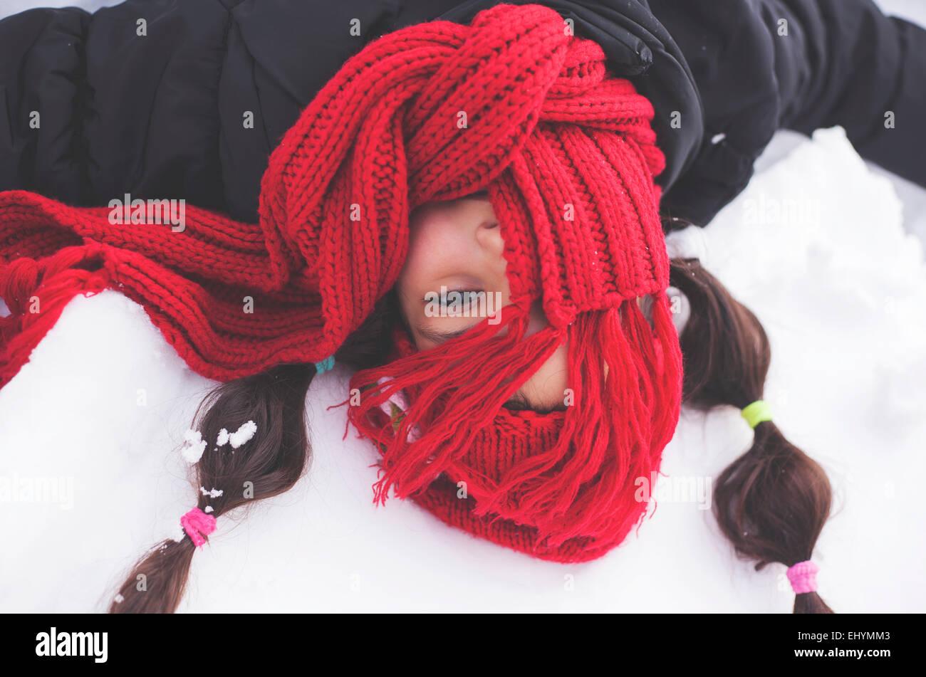Fille avec écharpe rouge covering face couché dans la neige Photo Stock