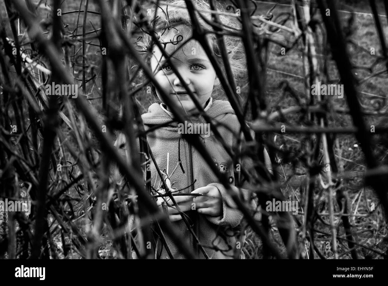 Fille de se cacher derrière les buissons Photo Stock