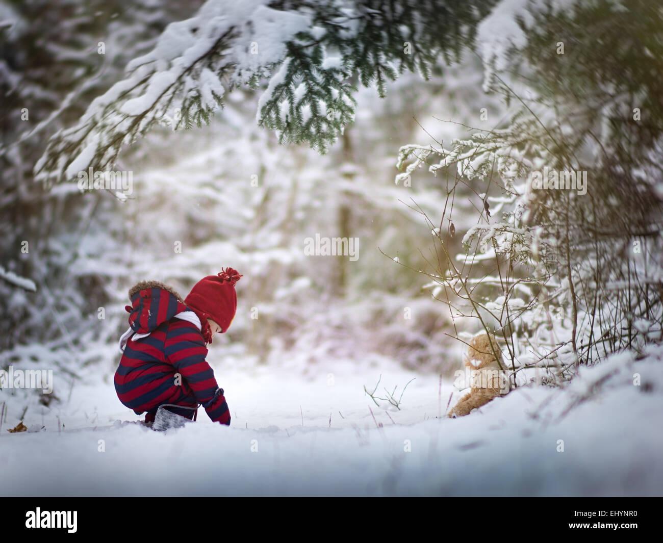 Bébé garçon dans la neige avec un ours en peluche Photo Stock