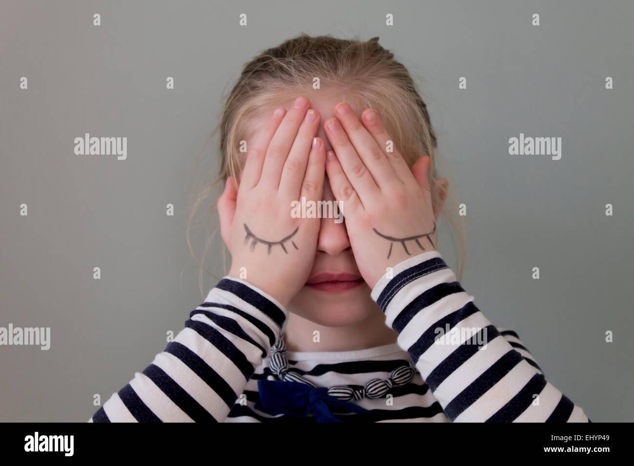 Girl couvrant ses yeux avec des mains qui ont des yeux tirés sur eux Photo Stock
