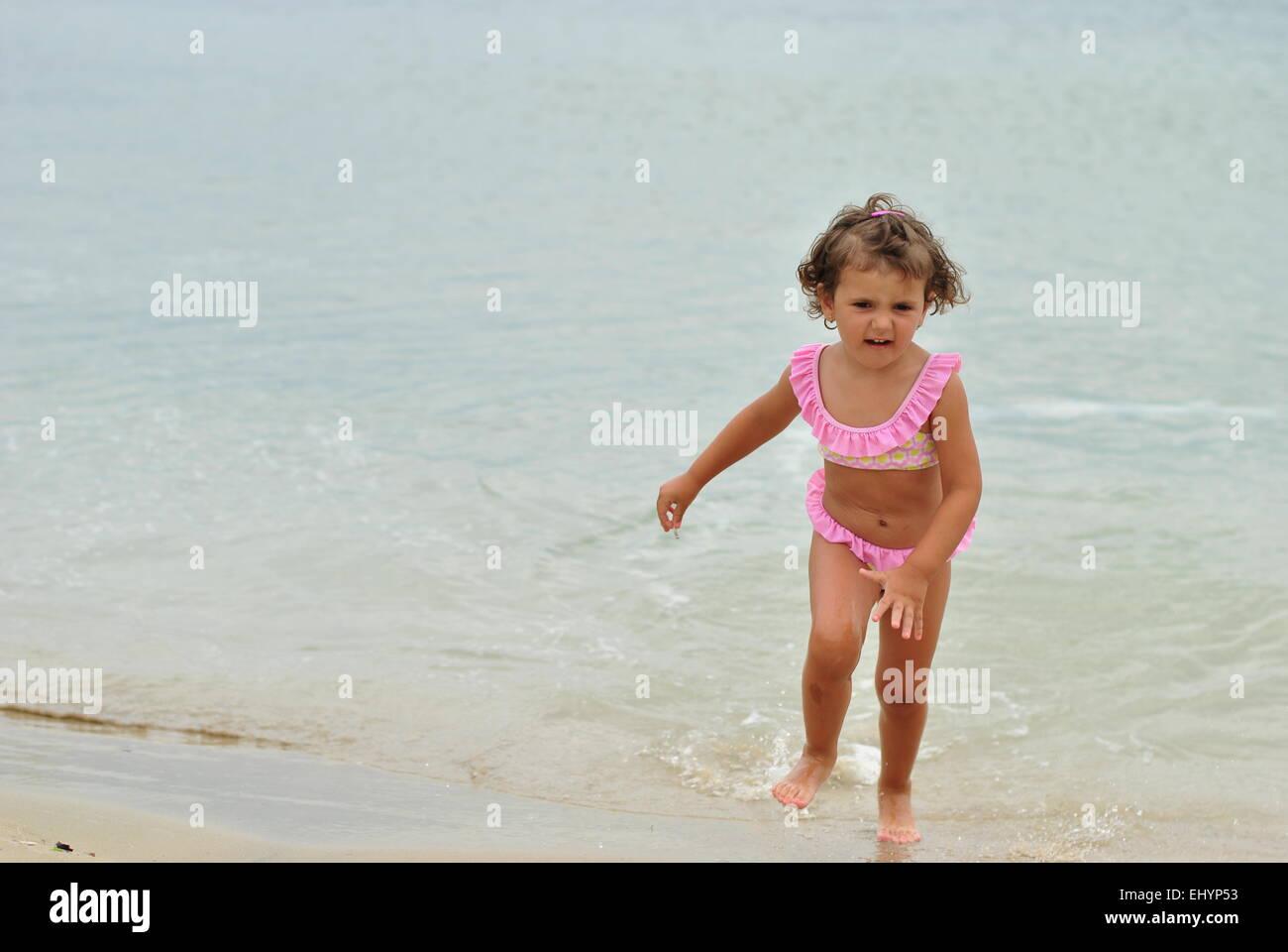 Girl in pink bikini court de mer Photo Stock