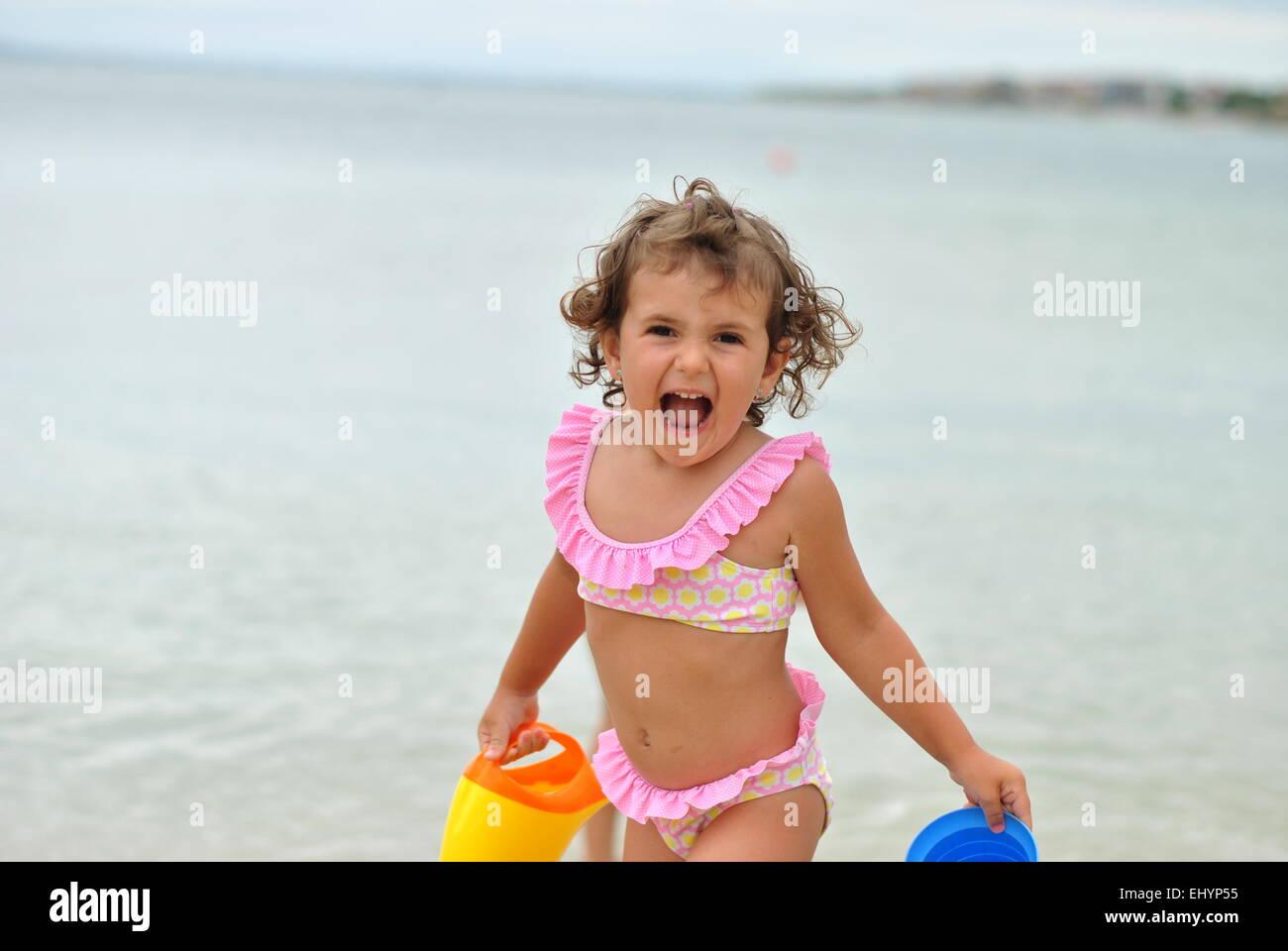 Girl in pink bikini jouant sur la plage Photo Stock