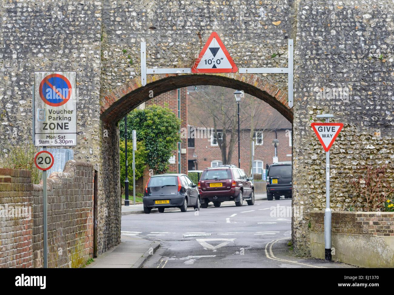 Restriction de hauteur sur une route étroite, sous un vieux mur de pierre. Photo Stock