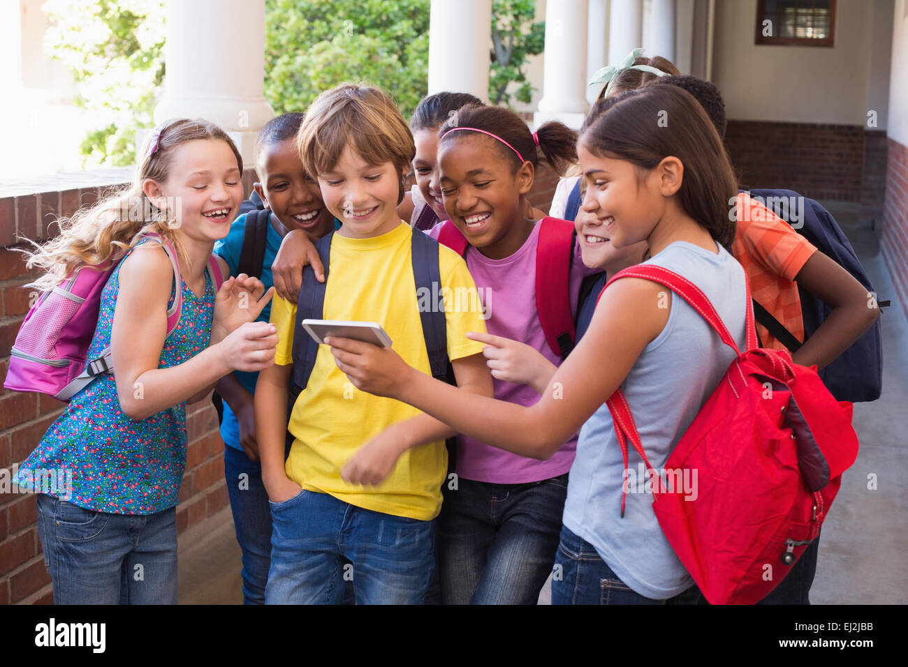 Les élèves à l'aide de téléphone mobile mignon Photo Stock
