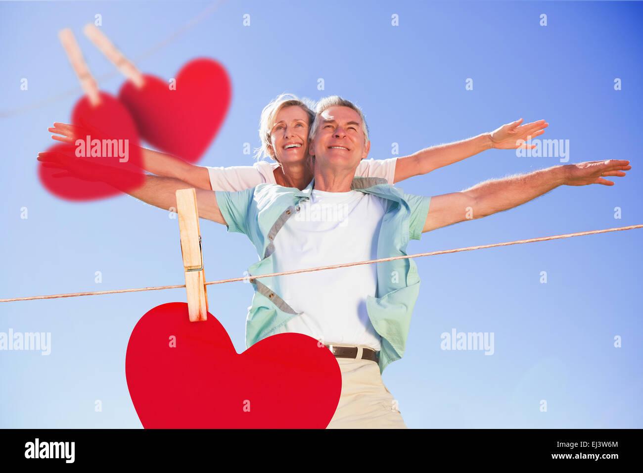 Image composite de happy senior man giving his partner un piggy back Photo Stock