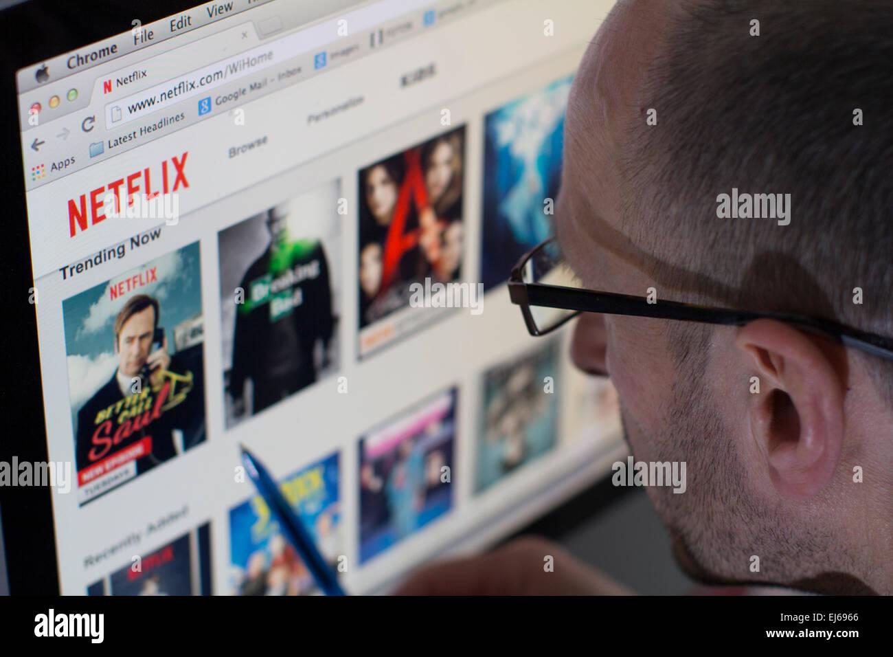 Homme à la recherche sur le site web du service de diffusion de télévision de Netflix Photo Stock