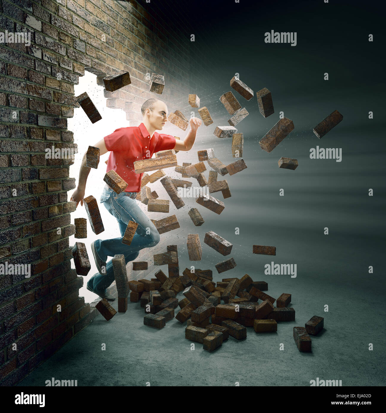 Jeune homme qui traverse un mur de brique Photo Stock