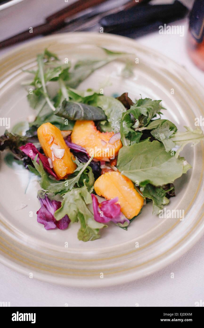 Une assiette de salade fraîche de feuilles et de tranches de pêche fraîche de fruits. Photo Stock