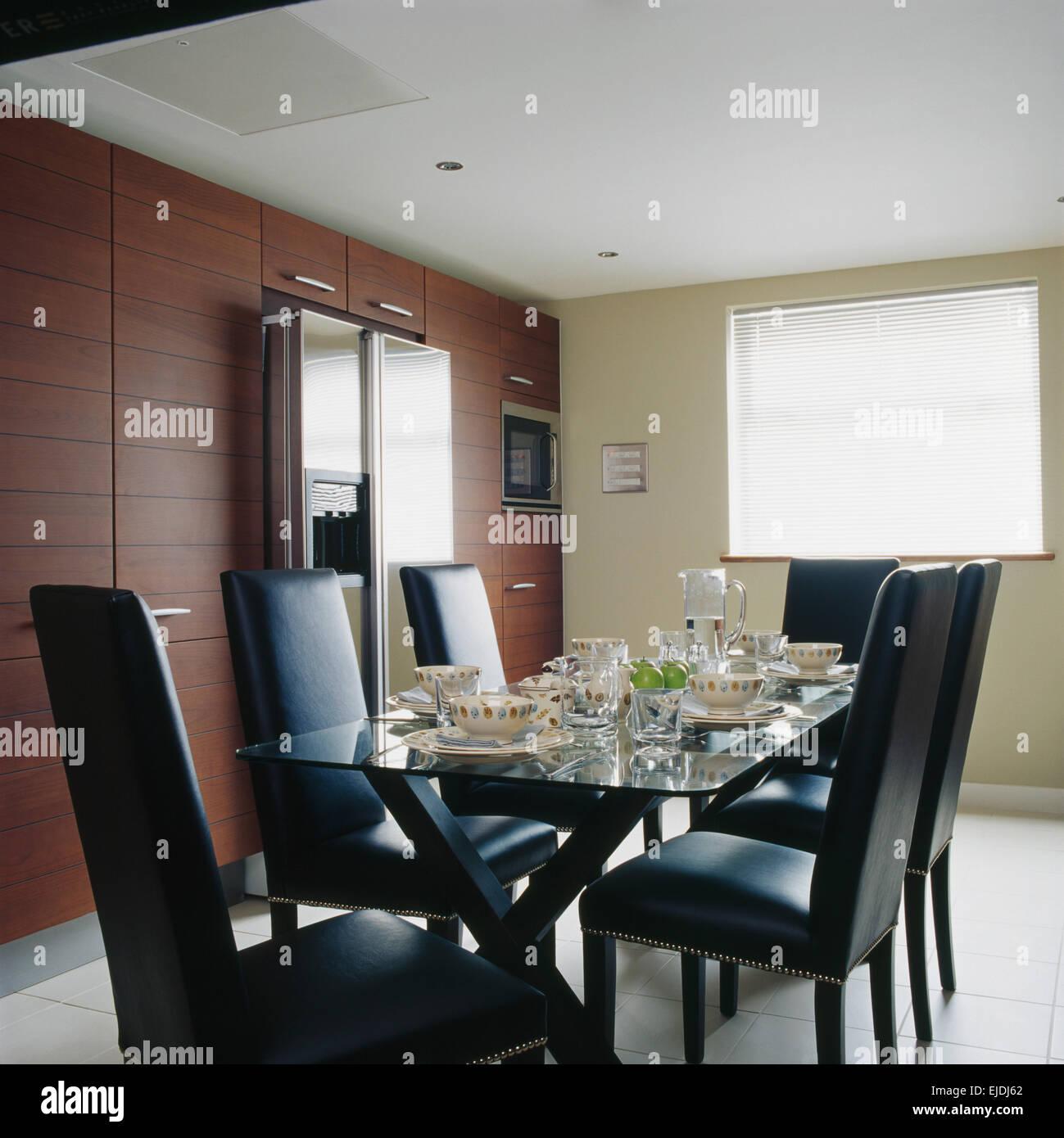 Chaises en cuir noir garni de verre à table à manger pour le dîner ...