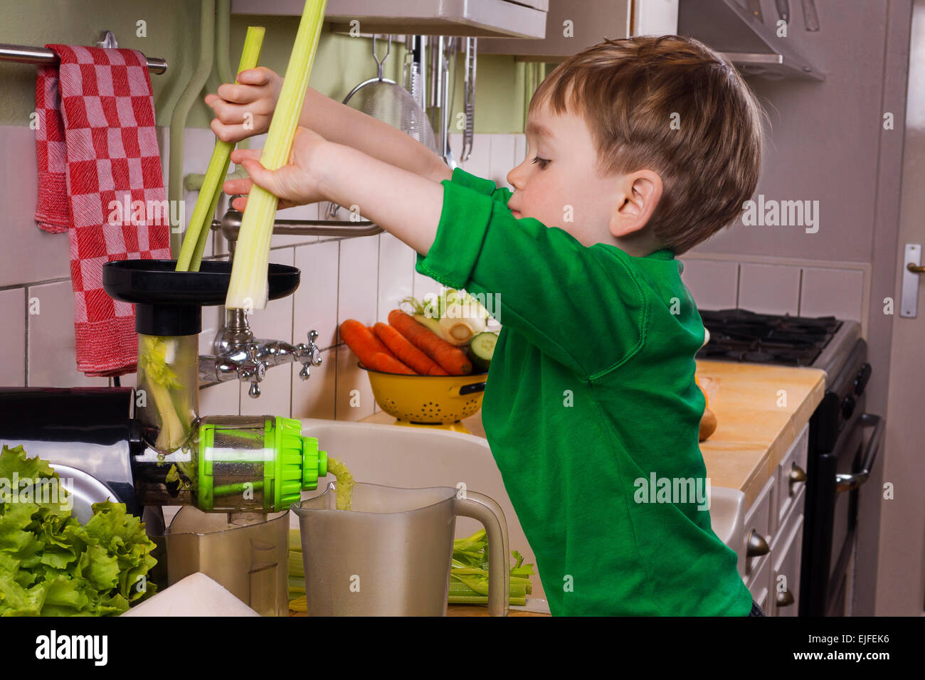 Petit garçon faisant jus vert Photo Stock