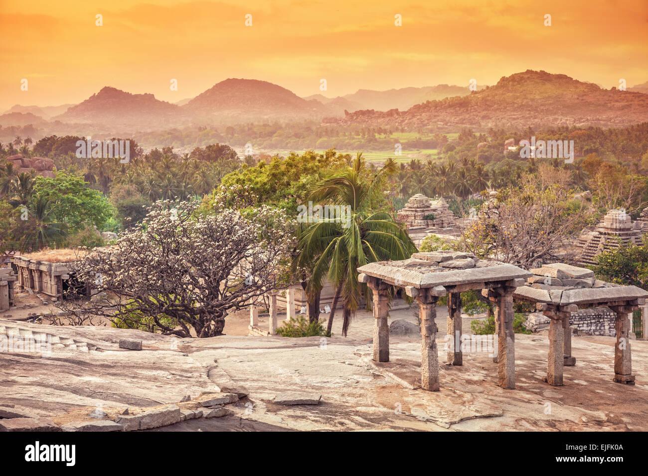 Ruines antiques sur Hemakuta hill au coucher du soleil orange sky à Hampi, Karnataka, Inde Photo Stock