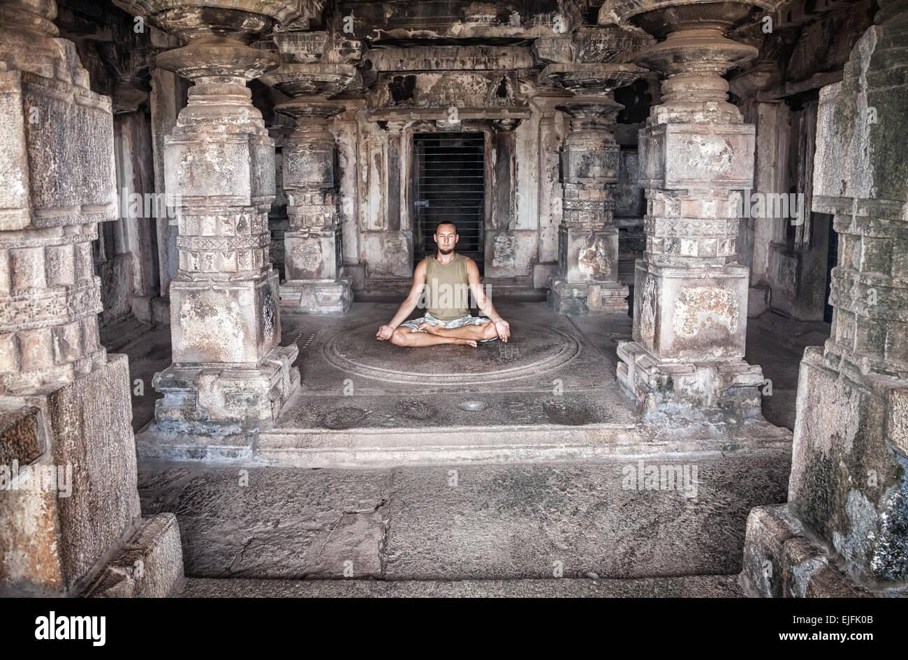 L'Homme faisant la méditation dans l'ancien temple de sculptures des colonnes dans Hampi, Karnataka, Photo Stock