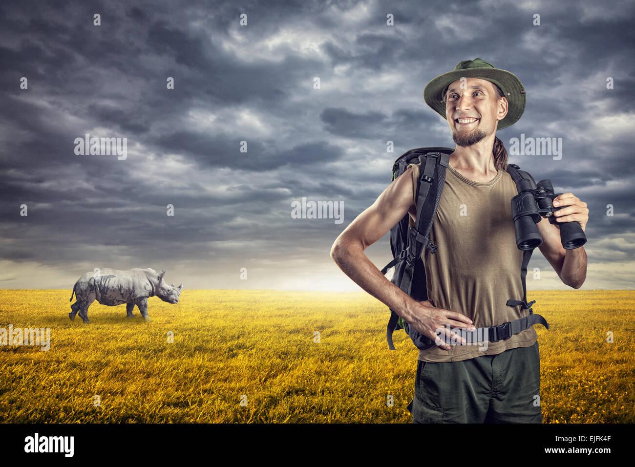 Homme avec des jumelles et rhino derrière dans les prairies au coucher du soleil Ciel couvert Photo Stock