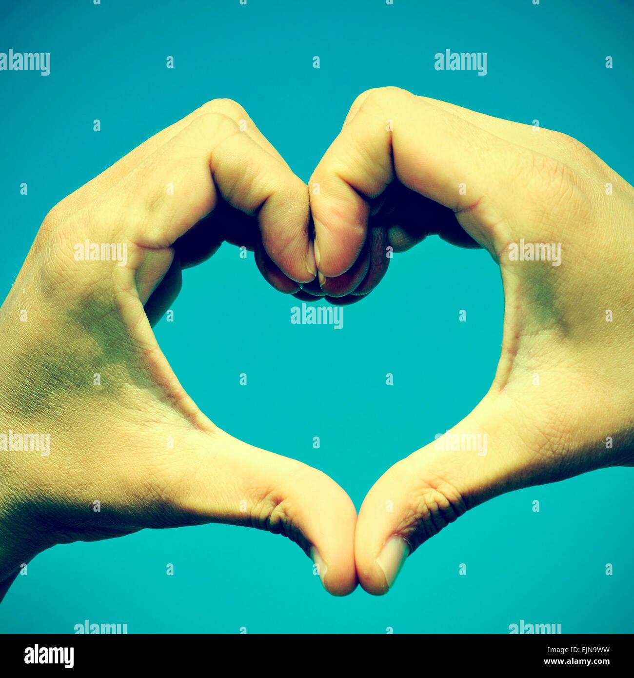 Photo de l'homme mains formant un coeur sur le ciel bleu, avec un effet rétro Photo Stock