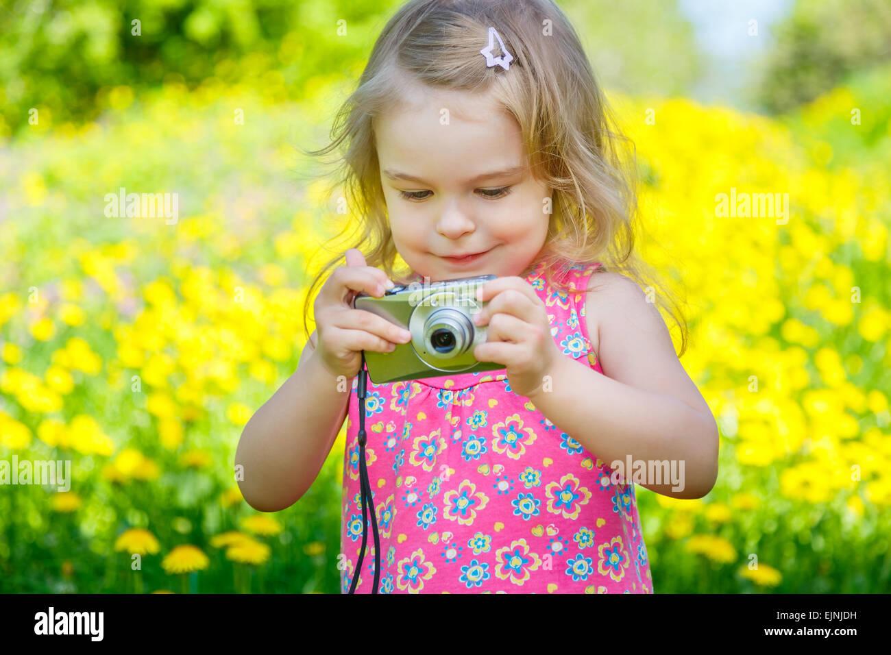 Petite fille à prendre des photos sur un pré Photo Stock