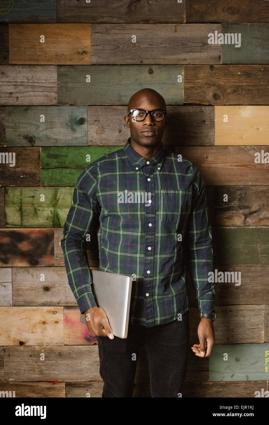Portrait of young African man with a laptop looking at camera en position debout contre un mur en bois à l'office. Photo Stock