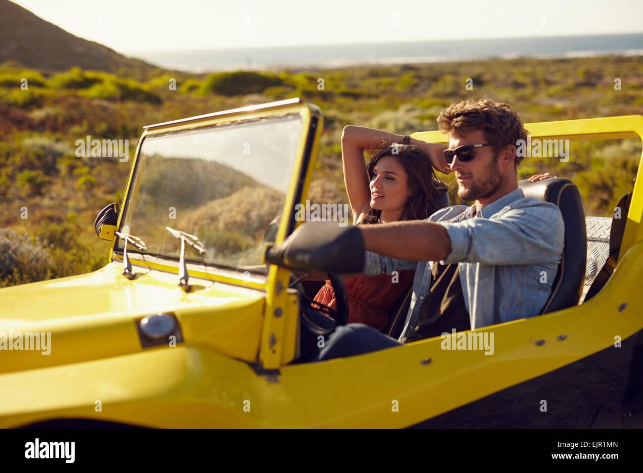 Jeune couple au volant de leur voiture sur un roadtrip. Beau jeune homme avec sa petite amie sur une maison de vacances. Photo Stock