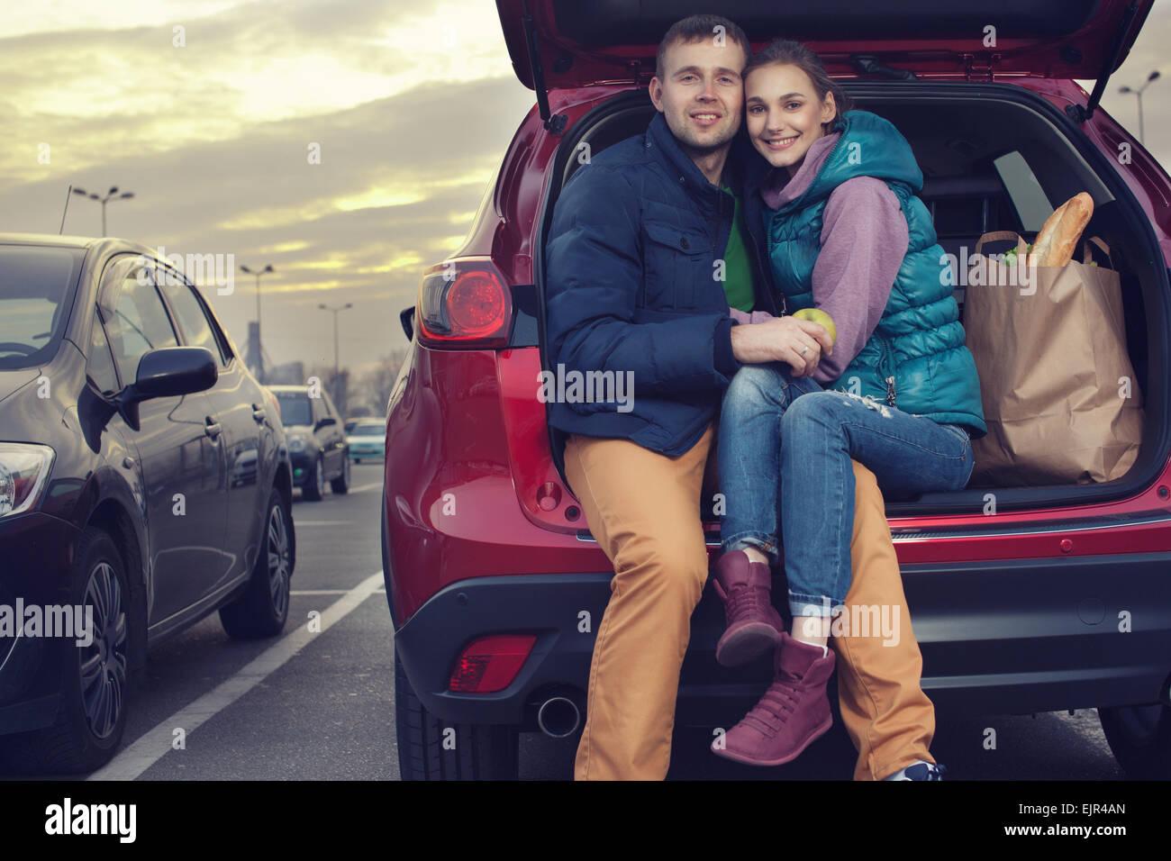 Heureux couple assis à coffre de voiture après le magasinage Photo Stock