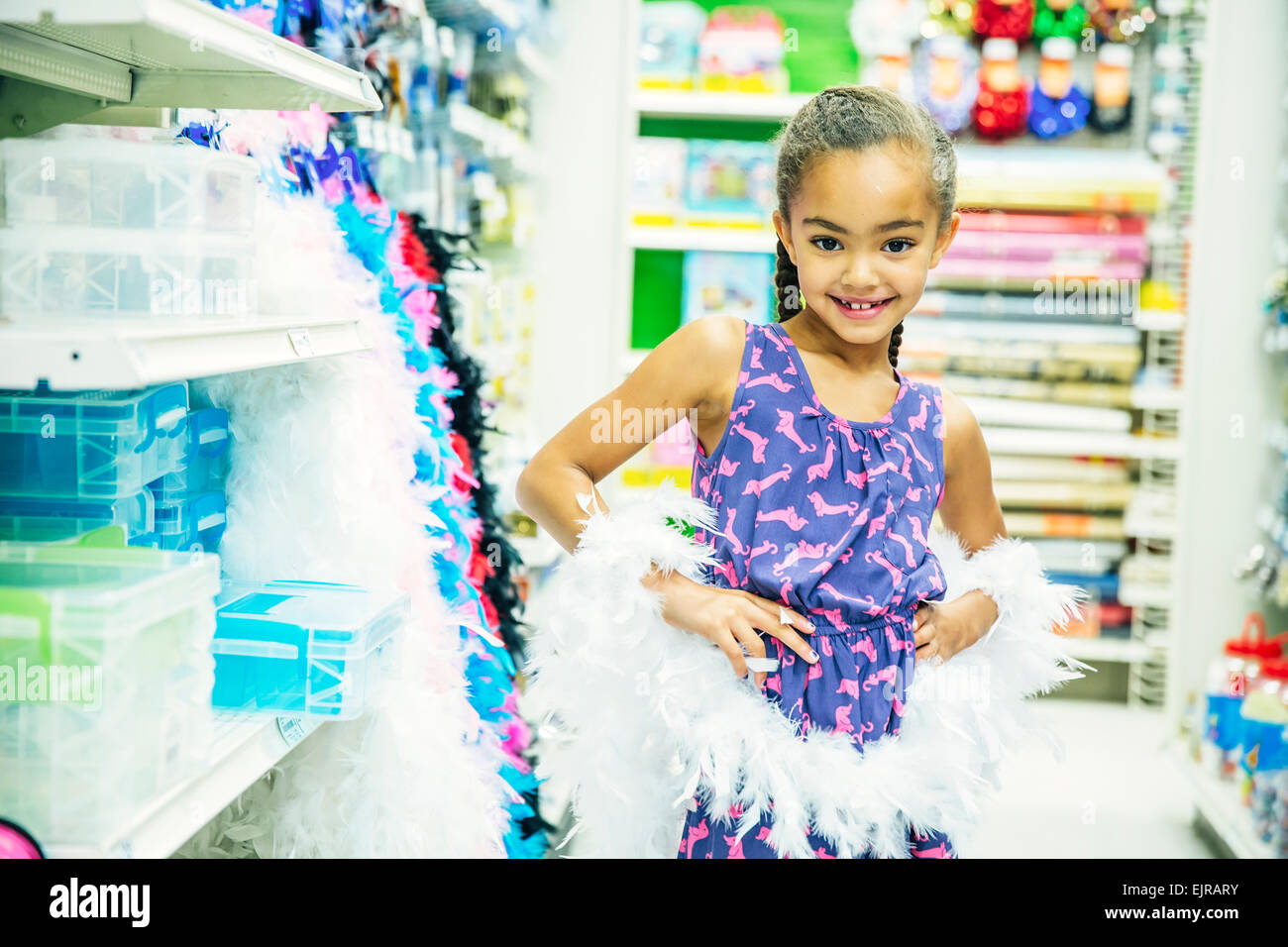 Mixed Race girl playing Dress-up in party store Banque D'Images