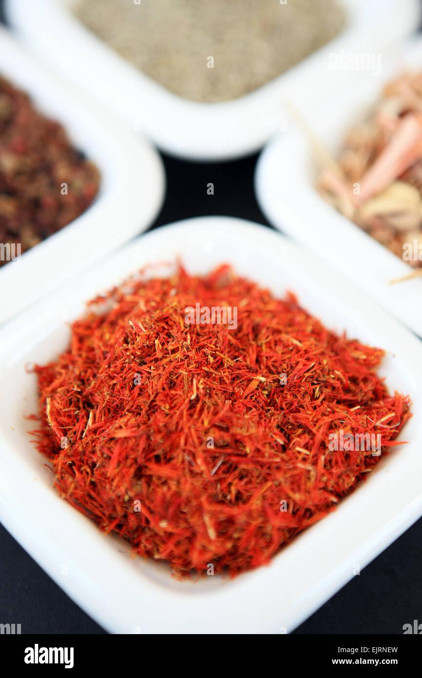 Le safran dans un petit plat blanc avec d'autres épices, qui tourne dans le sens horaire à partir du safran, poivre Banque D'Images