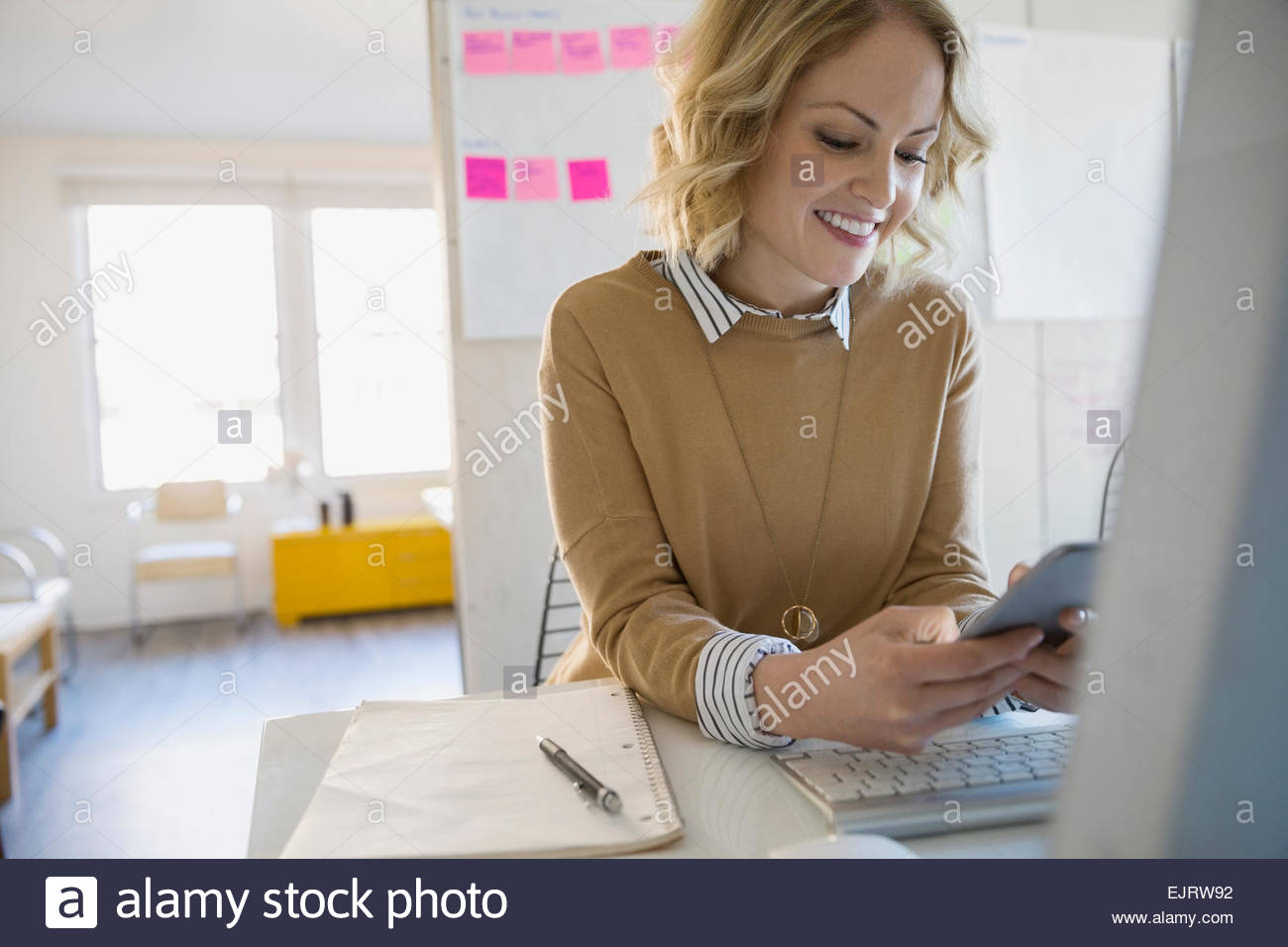 Smiling businesswoman text messaging dans la salle de conférence Photo Stock