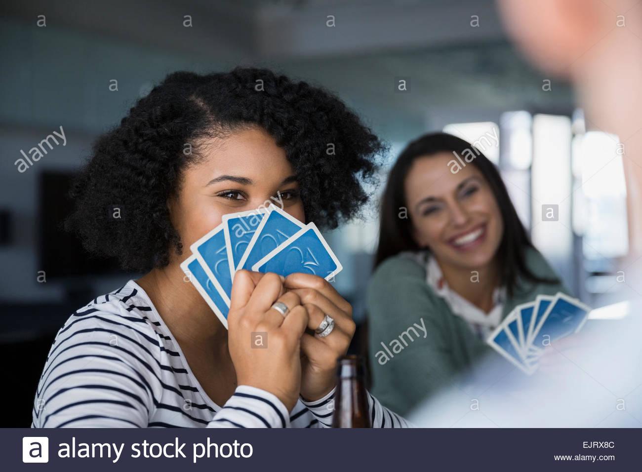 Femme de se cacher derrière des cartes à jouer Photo Stock