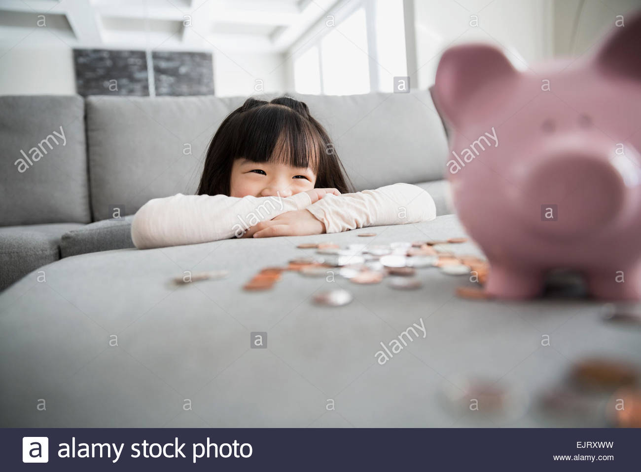 Smiling girl with piggy bank et pièces Banque D'Images