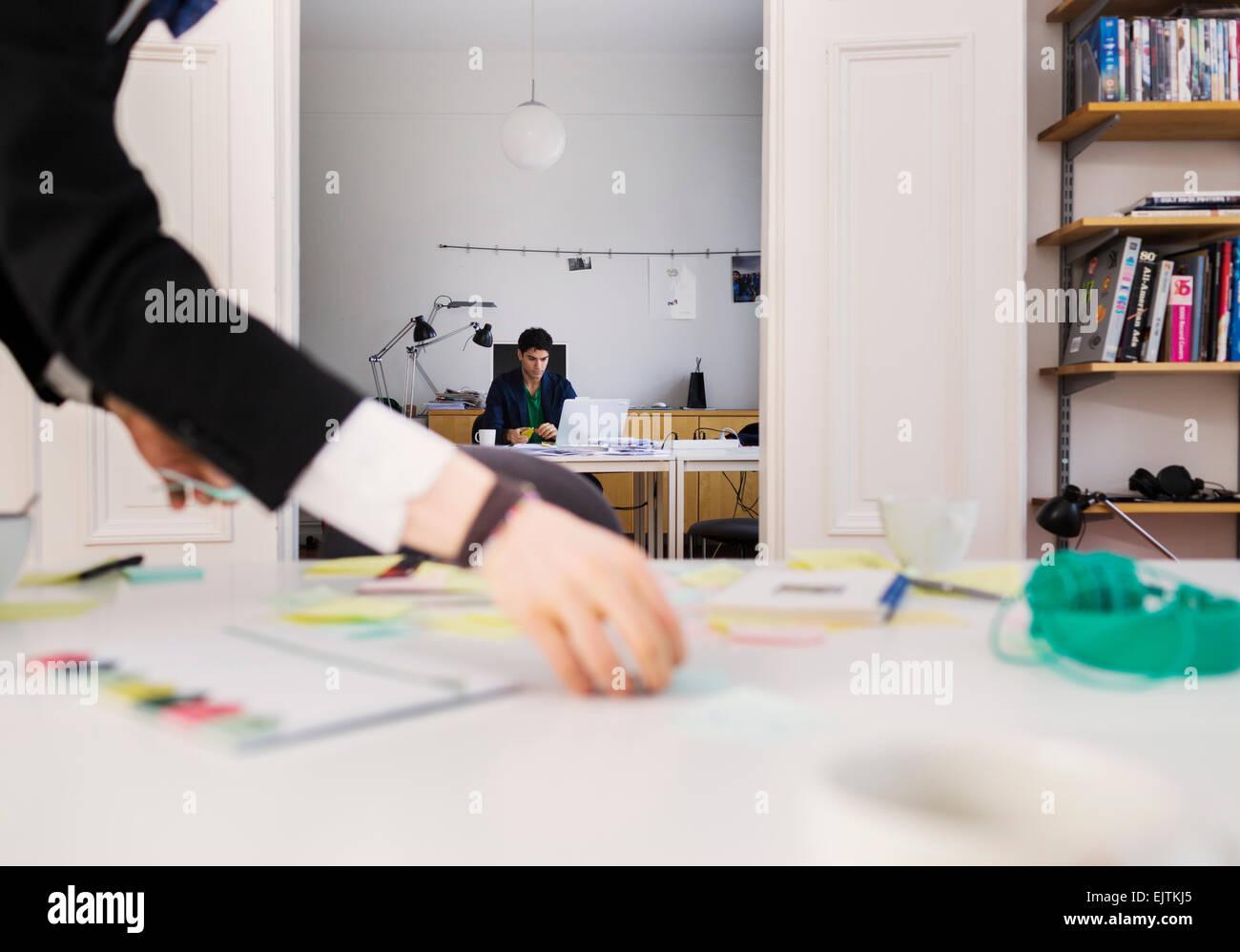 Portrait of businessman's hand holding tandis que les notes de rappel collègue travaillant en arrière Photo Stock
